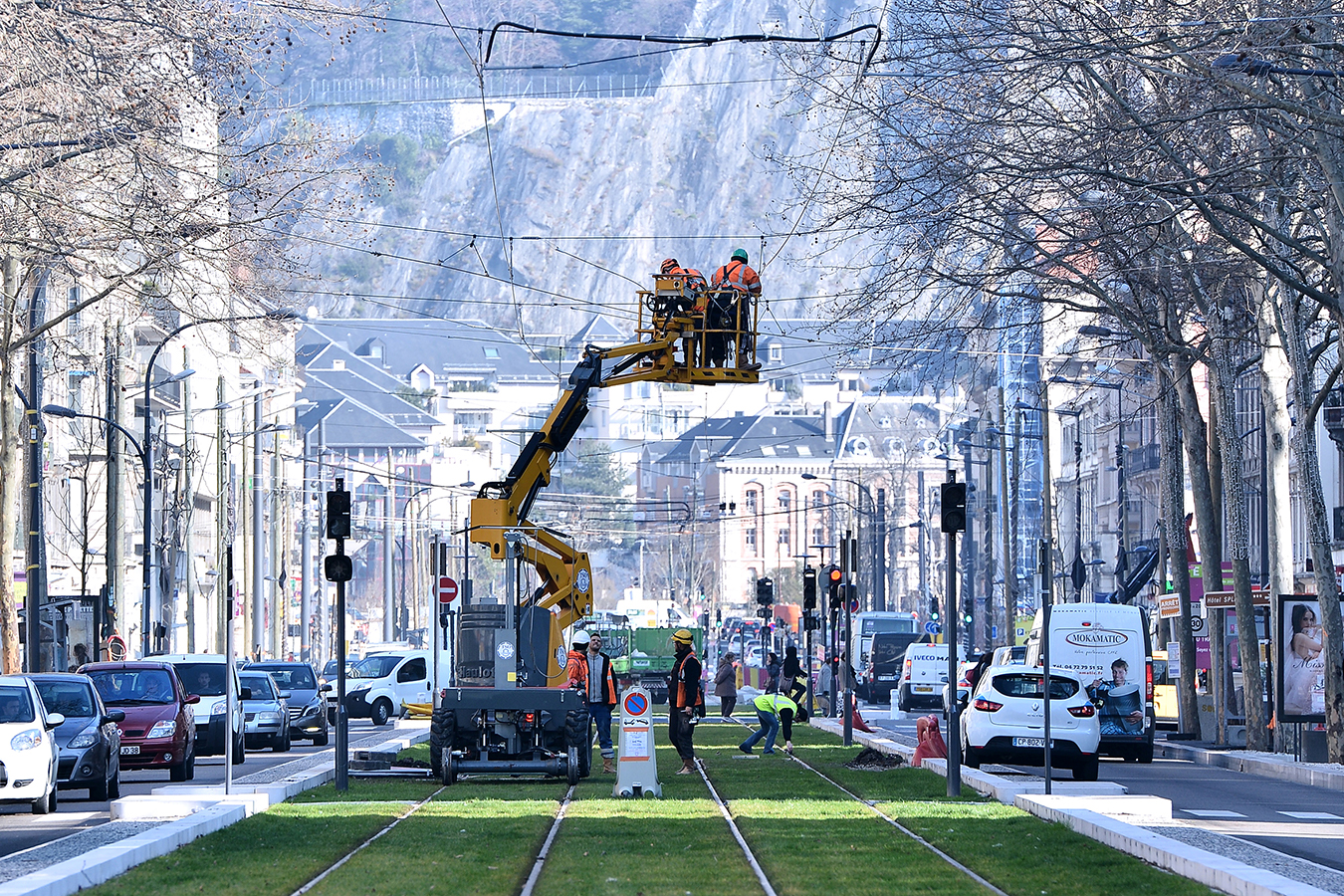 Deux ouvriers sur un engin réalise l'électrification d'une ligne de tramway.